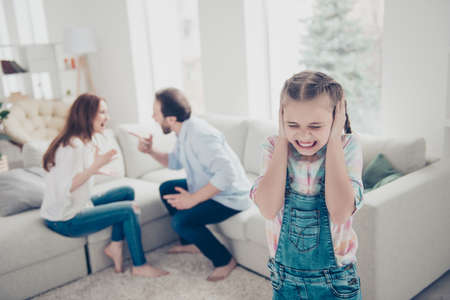 Portrait of crying unhappy schoolgirl cover ears with hands because of rage violent parents yelling sitting on sofa on blurred background. Wife husband relations concept