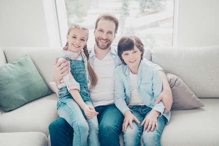 Portrait of family with one parent, positive joyful father embracing two kids sitting indoor on sofa wearing casual outfit enjoying free time together. Understanding upbringing concept