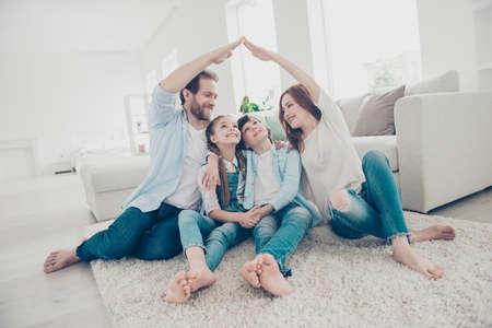 Nieuwbouw woonhuis aankoop appartement concept. Stijlvolle volledige familie met twee kinderen zittend op een tapijt, mama en papa dak figuur met handen armen boven het hoofd maken