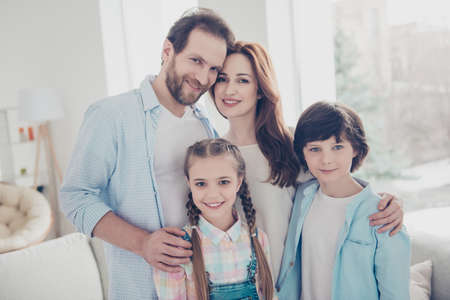 Portrait of attractive joyful family with two kids, handsome man beautiful girls with trendy stylish hairstyle in casual oufits looking at camera. Understanding trust support care concept Stock Photo
