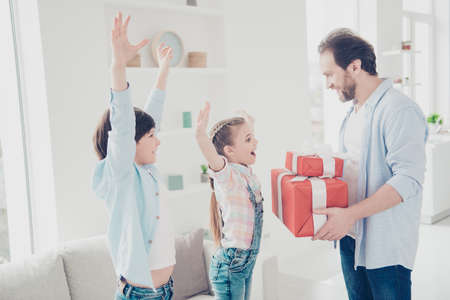 Wow! Best handsome father prepare two gift cases in red package with bow giving to impressed shocked astonished kids holding raised hands enjoying surprise. Family with one parent concept