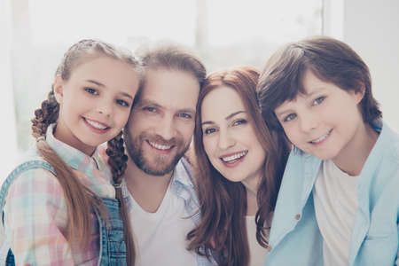 Head shot portrait of lovely full family with beaming smiles in casual outfits looking at camera enjoying weekend indoor. Understanding support trust idyllic concept