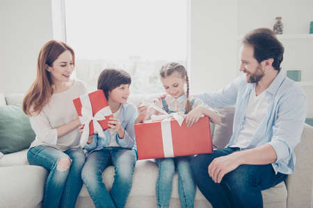 Portrait of careful family unpacking gift cases in red package with bow together sitting on sofa indoor enjoying surprise holding presents in hands speaking talking having fun Stock Photo