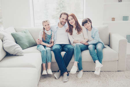 Full size portrait of trendy lovely family in casual outfits, four people two kids wearing sneakers jeans sitting in modern white livingroom in apartment looking at camera Stock Photo
