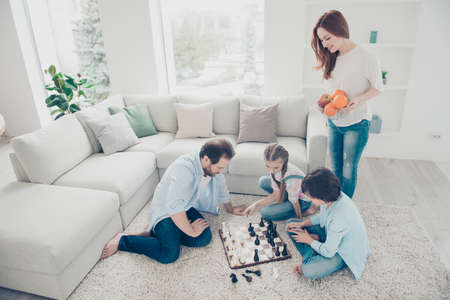 Portrait of thoughtful dad and two kids playing chess board game planning strategy sitting on carpet near sofa, smiling mom bringing plate with fruits for gamers. Idyllic concept Stock Photo - 104543392