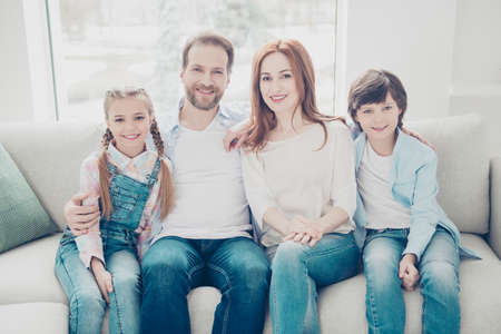Portrait of stylish attractive family with two children in casual outfit jeans sitting in living room indoor enjoying time together looking at camera. Domestic lifestyle concept