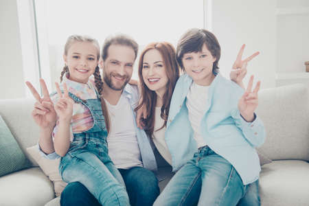 Portrait of friendly peaceful four people, beautiful mom handsome dad two kids sitting on couch indoor hugging gesturing v-sign looking at camera