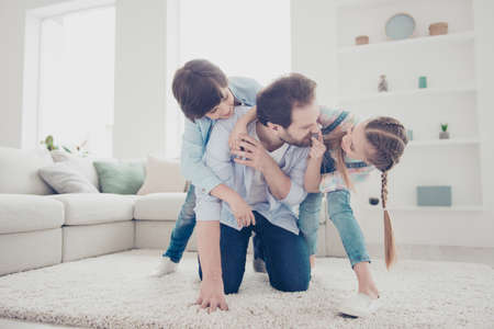 Portrait of stylish family with one parent, father playing with two foolish playful kids carrying on back standing on knees enjoying funny time indoor in modern white living room
