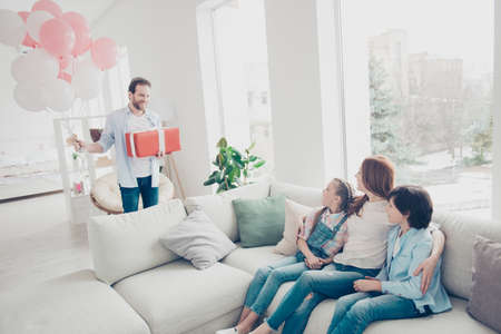 Portrait of husband prepare packed gift case for wife two kids holding air ballons, lovely mom sitting on sofa in modern white living room embracing children meeting daddy with excited emotions