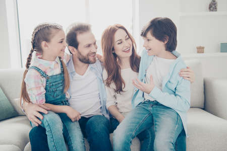 Portrait of full family enjoying free time indoor hugging, schoolboy telling news story to mum daddy and sister, kids sitting on parents legs. Understanding support trust idyllic concept Stock Photo