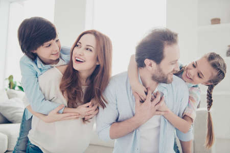 Portrait of positive funny family enjoying time indoor playing with kids carrying on back schoolgirl schoolboy looking at each other. Togetherness friendship domestic lifestyle concept Stock Photo - 104543615