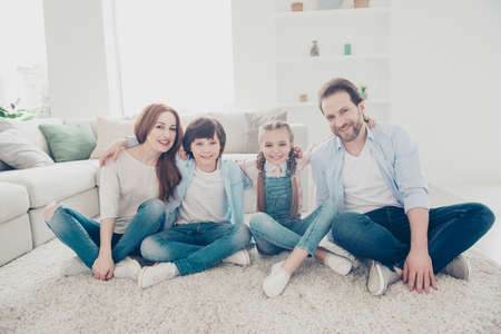 Portrait of friendly stylish family sitting on the floor near sofa with crossed legs embracing looking at camera wearing jeans sneakers casual outfits. Togetherness concept Stock Photo