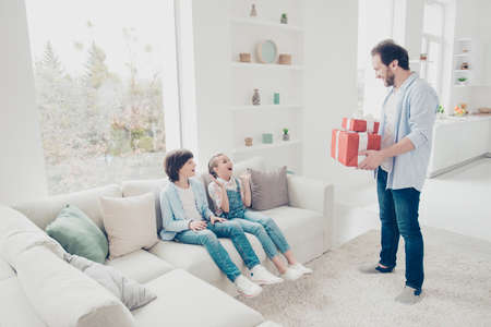 Portrait of best handsome father prepare two gift cases in red package with bow giving to impressed shocked kids sitting on couch in modern white apartment with interior. Family with one parent concept