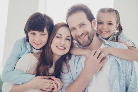 Head shot portrait of four lovely people, full beautiful family, parents carrying on back two kids. Generation understanding trust support affection tru big love concept