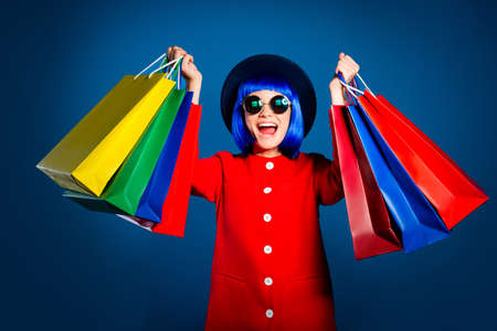 Portrait of successful lucky girl in red coat yelling with open mouth showing gesturing many colorful shopping packets in hands isolated on blue background with shadow light 写真素材