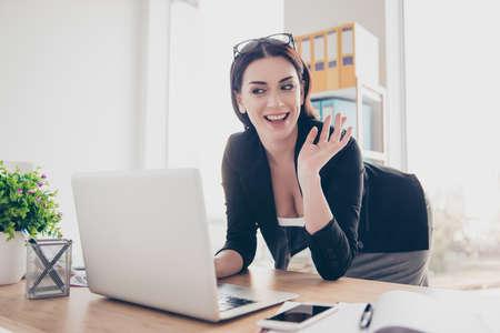 Portret przyjaznej kobiety pochylającej się nad biurkiem, wskazując dłoń znak cześć, mając rozmowę wideo z kochankiem, demonstruje duży