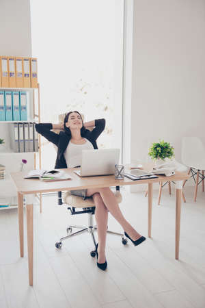 Full size portrait of sexy trendy woman wearing high heel shoes skirt sitting in modern office holding hands behind head planning vacation weekend trip journey