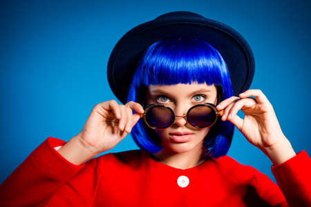 Head shot portrait of attractive pretty elegant girl in headwear looking out summer glasses with attentive sight holding eyelets with two hands isolated on blue background