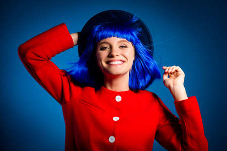 Portrait of toothy positive girl with flying hair holding hat .