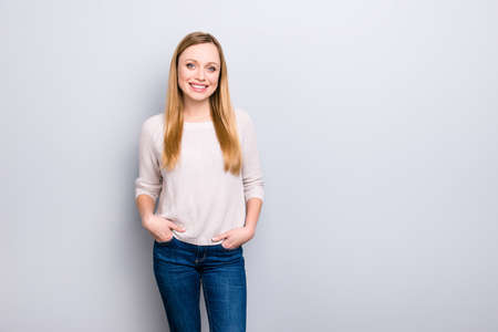 Portrait with copy space empty place for product of cheerful pretty girl holding two hands in pockets of pants looking at camera isolated on grey background