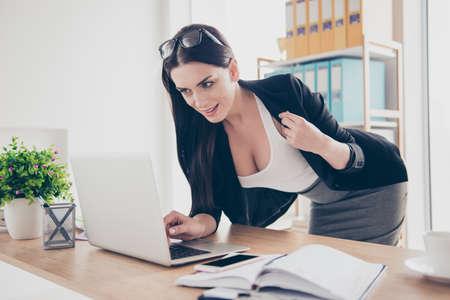 Portrait de femme charmante se penchant près de bureau montrant sa grande veste ouverte décolleté ayant un appel vidéo avec amant