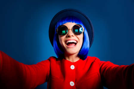 Self portrait of cheerful positive woman with beaming smile shooting selfie on front camera with two hands laughing loud isolated on blue background.