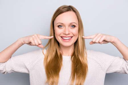 Porträt des freudigen zufriedenen Mädchens gestikuliert ihre strahlenden weißen gesunden Zähne mit zwei Zeigefingern, die Kamera lokalisiert auf grauem Hintergrund betrachten. Kieferorthopädisches Konzept