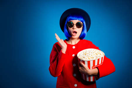 OMG! Portrait of shocked worried girl with wide open mouth in elegant outfit holding big bucket of pop-corn in hand isolated on blue background. Entertainment rest relax leisure concept