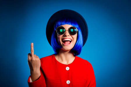 Portrait of cheerful provocative girl in headwear eyewear gesturing fuck off sign with middle finger isolated on blue background. Conflict insult dispute concept