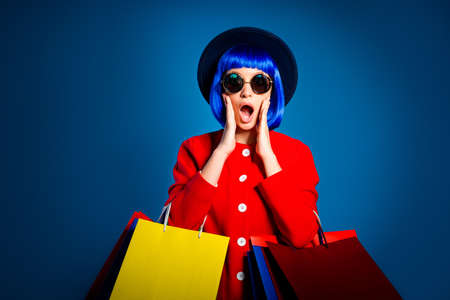 Portrait of chocked woman with wide open mouth having problem holding colorful packets waste all money, marketing commerce concept, isolated on blue background with shadow and light