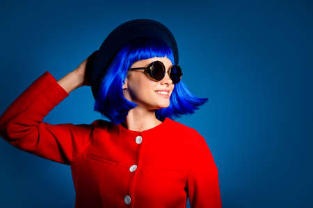 Portrait of pretty attractive woman moving with head holding hat with hands having flying hair isolated on blue background. Sun shine freedom concept 写真素材