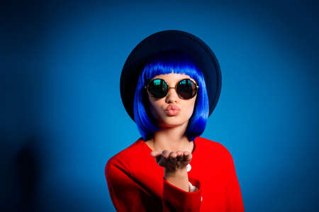 Portrait of lovely cute  girl in eyewear headwear blue wig sending air kiss with pout lips palm at camera isolated on yellow background with light and shadow 写真素材