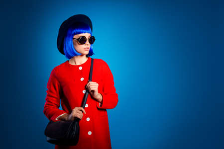 Portrait of pretty charming girl in eyewear head wear in red coat with bag on shoulder looking away having rest vacation weekend isolated on blue background with copy space empty place Stok Fotoğraf