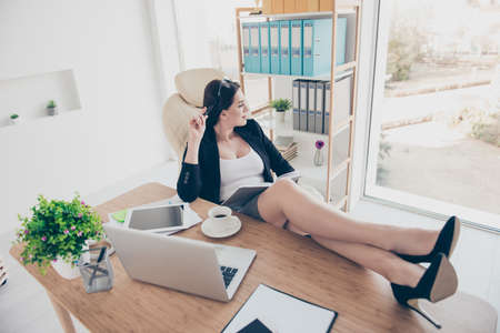 Portrait of dreamy pensive woman putting sexy legs on table wearing stilettos looking at window having notepad and pen in hands dreaming about vacation weekend planning journey trip Standard-Bild