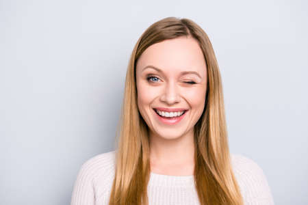 Head shot portrait of charming pretty laughter lovely girl in good mood winking with one eye isolated on grey background