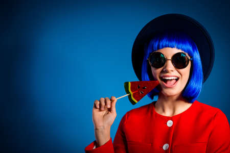 Portrait with copyspace empty place of cheerful positive girl having holding tasty delicious lolli pop on stick near open mouth looking at camera isolated on blue background