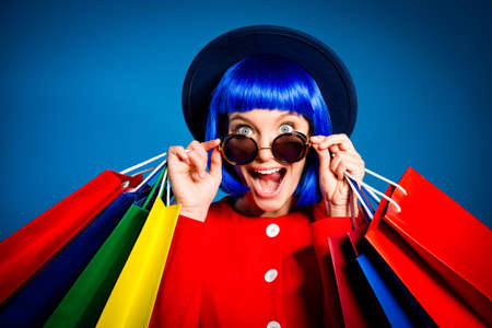 Portrait of surprised admired woman looking out glasses with wide open eyes mouth screaming holding colorful packets in hands enjoying seasonal sale having pleasure. Delight inspiration concept