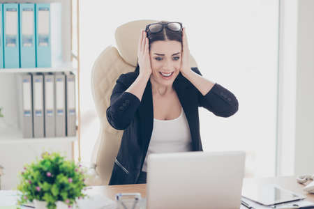 Unbelievable! Portrait of cheerful positive girl with unexpected reaction holding hands on head enjoying successful results having good news information sitting in modern workstation Stock Photo