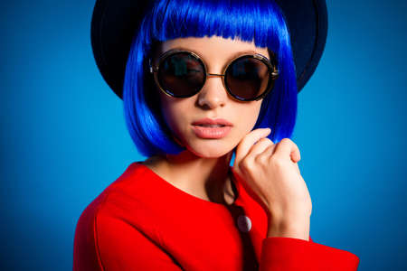 Cropped closeup portrait of dreamy gentle elegant girl in eyewear modern wig isolated on blue background with light and shadow 写真素材