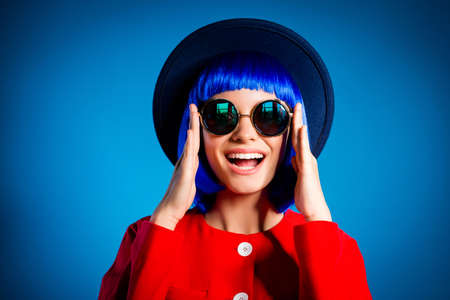 Head shot portrait of positive toothy girl with beaming smile laughing laud sincerely fixing correcting summer eyeglasses on face isolated on blue background