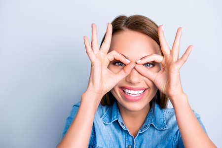 Close up portrait of ffunny creative woman with beaming smile making binoculars with fingers on her face isolated on grey background Stockfoto