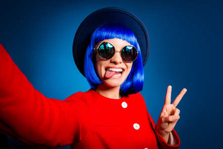 Self portrait of cheerful childish blogger shooting selfie on front camera gesturing v-sign showing tongue-out isolated on blue background. Rest relax weekend holiday concept