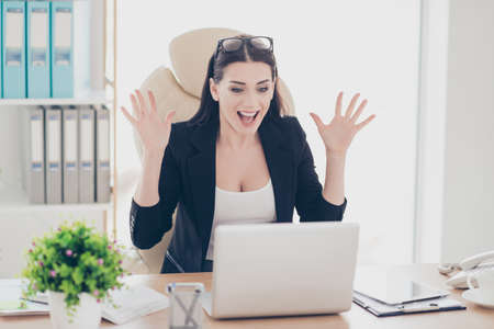 Portrait of glad cheerful yelling financier gesturing with hands looking at screen of laptop celebrating a great triumph big effective results having fun sitting in modern workstation