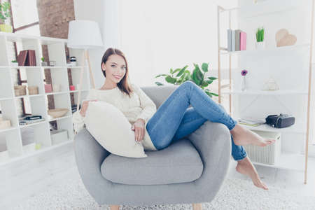 Portrait of pretty charming girl  sitting on armchair in modern livingroom looking at camera enjoying new cozy apartment