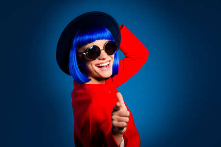 Hey you, baby! girl in eyeglasses head wear pointing forefinger at camera isolated on blue background.