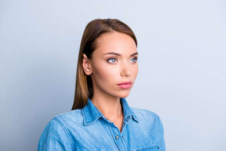 Portrait of half turned serious woman in jeans shirt with concentrated thoughtful expression isolated on grey background Stock Photo