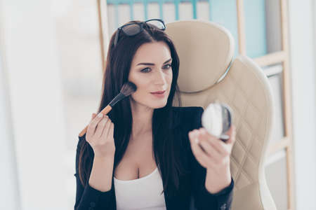Portrait of trendy pretty woman applying rouge on cheeks with brush holding little mirror in hand while having time out pause feetime preparing for meeting date Imagens