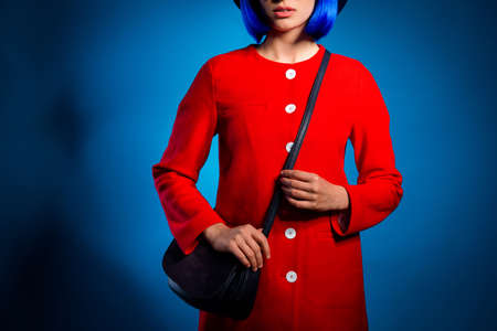 Cropped portrait of fashionable pretty woman in red outfit with black bag on shoulder isolated in bright blue background. Wear cloth concept Stock Photo