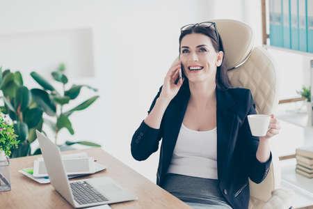 Portrait of positive laughing woman having fun drinking tea holding mug in hands speaking by smart phone with friends looking away enjoying conversation coffee break Stockfoto