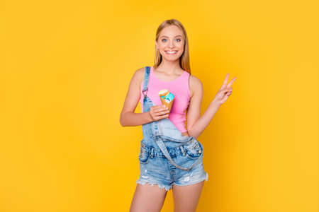 Portrait of cheerful charming girl in denim overall having delicious ice cream scoops in waffle cone gesturing v-sign with two fingers isolated on yellow background, looking at camera